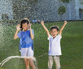 Excited kids has fun playing in water fountain — Stock Photo