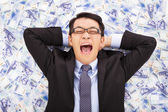 Happy  business man lying on the stacks of new taiwan dollar — Stock Photo