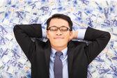 Business man enjoying and lying on the stacks of money — Stock Photo