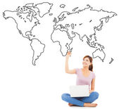 Smiling young woman sitting and drawing global map — Stock Photo