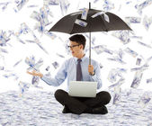 Business man holding a umbrella and catching money — Stock Photo