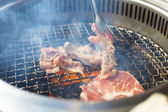 Closeup of meat on a grill or barbecue with smog — Stock Photo