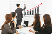 Group of business people discussing sales on whiteboard — Stock Photo