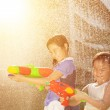 Cheerful girls playing water guns in the park — Stock Photo