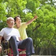 Asian senior man sitting on a wheelchair with his wife — Stock Photo #50454237