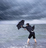 business man holding a umbrella to resist rainstorm  — Stock Photo