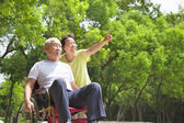 Asian senior man sitting on a wheelchair with his wife — Stock Photo