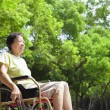 Asian senior woman sitting on a wheelchair in the park — Stock Photo #50531943