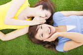 Two sisters  whispering gossip on the grass — Stock Photo