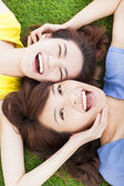 Two pleasure young woman lying on grass — ストック写真