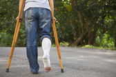 Young asian man on crutches with tree background — Stock Photo