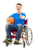 Hopeful young man sitting on a wheelchair with a basketball — Stock Photo