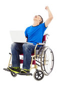 young man sitting on a wheelchair and  excited to raise arm — Stock Photo