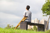 Injured Man with Crutches sitting on a bench — Stock Photo