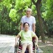 Senior woman sitting on a wheelchair with his husband — Stock Photo #50972949