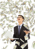 Happy business man holding a laptop with money rain — Stock Photo