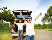 Happy children and father raise arms with their car  — Stock Photo