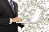 Businessman holding a laptop with money rain — Stock Photo