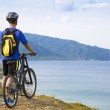 Young man standing on the mountain with bike — Stock Photo #51146333