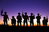 Soldiers silhouettes against a sunset or sunrise background  — Stok fotoğraf