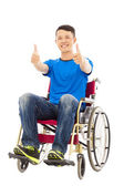 Happy young man sitting on a wheelchair and thumb up — Stock Photo