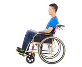 Hopeful young man sitting on a wheelchair in studio — Stock Photo