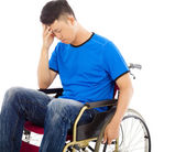 Upset handicapped man sitting on a wheelchair — Stock Photo