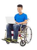 Hopeful young man sitting on a wheelchair with a laptop — Stock Photo