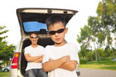 Cool boy and father across arms with their car  — Stock Photo