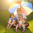 Father and daughters sitting on a meadow with colorful umbrella — Stock Photo
