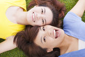 Two asian pleasure young woman lying on grass — Stock fotografie
