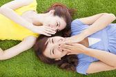 Two asian sisters whispering gossip on the grass — Stock Photo