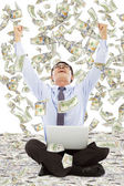 Exciting young businessman raise hands with money — Stock Photo