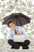 Happy business man sitting on floor with us dollar rain — Stock Photo