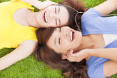Two pretty young woman lying on grassland and listening music  — Stock Photo