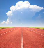 Red running track over blue sky and clouds — Stock Photo