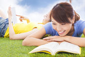 Smiling pretty students lying on the grassland with books — Stock Photo