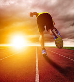Athletic young man running on race track with sunset background — Stock Photo