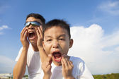 Father and son making a grimace together in the park — Stock Photo