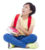 Young student girl sitting on floor with book — Stock Photo
