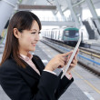 Young business woman using touch pad in the train station — Stock Photo #5431058