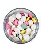 Kolorowe pigułki w przezroczyste szkło na białym tle, góry — Zdjęcie stockowe
