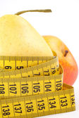 Pear and apple with a measuring tape — Stock Photo