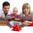 Happy young family lying on the floor on red cushions, white bac — Stock Photo