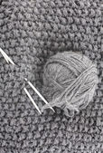 Ball of wool for knitting and needles on the knitted items — Stock Photo
