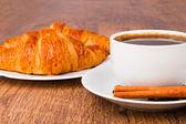 与一个牛角面包和新鲜的咖啡豆杯咖啡 — 图库照片