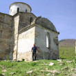 Stock Photo: Man near the old church in Caucasian mountains