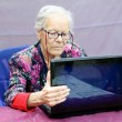 图库照片: Grandmother consult pc