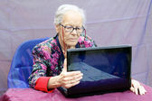 Grandmother consult the pc — Stock Photo