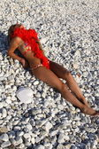 Beautiful girl with red feather boa on the beach — 图库照片